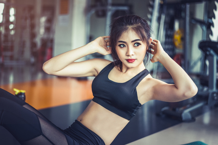 Side view of Asian fitness girl doing crunch twist at fitness gym. Sports and workout concept. Fitness gym and beauty theme.