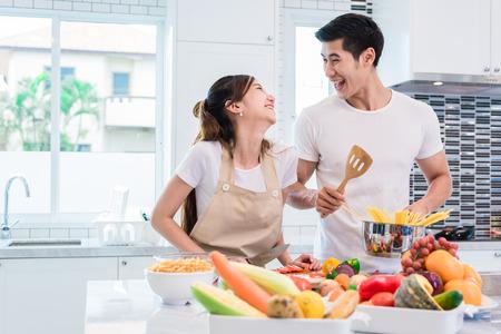 Amantes ou pares asiáticos que cozinham tão engraçados junto na cozinha com completamente do ingrediente na tabela. Conceito de lua de mel e felicidade. Dia dos Namorados e Sweet Home