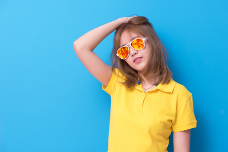 Asian woman fashion posing with fashion eye glasses on the blue background. Woman wearing yellow polo shirt and yellow orange glasses. Beauty and modern fashion concept.