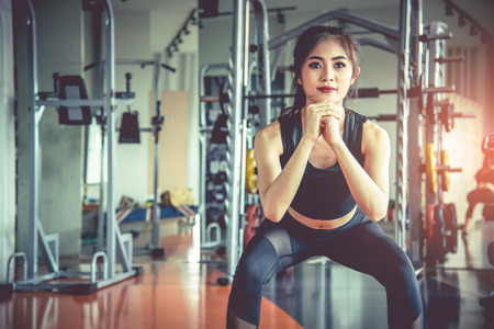 Young Asian woman doing squat workout for fat burning and diet in fitness sports gym with sports equipment in background. Beauty and body build up concept. Sports club and Aerobic theme. Stock Photo