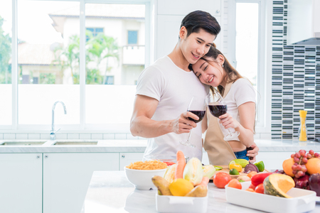 Asian lovers or couples drinking wine in kitchen room at home. Love and happiness concept Sweet honeymoon and Valentine day theme Standard-Bild