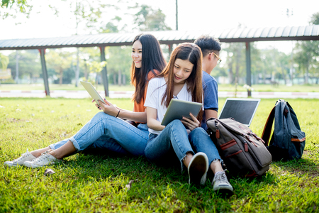 Group of Asian college student using tablet and laptop on grass field at outdoors. Technology and Education learning concept. Future Technology and Modern entertainment concept. Edutainment theme.