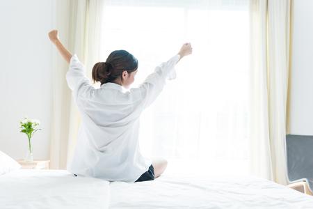 Achtermening van zich vrouw het uitrekken in ochtend na ontwaken op bed dichtbij venster. Vakantie en ontspanning concept. Luie dag en werkdag concept. Bureaumens en arbeider in dagelijks levensthema