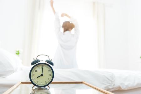 Vista posterior de la mujer que estira por mañana después de despertar en cama cerca de la ventana con el despertador. Concepto de vacaciones y relax Día tranquilo y concepto de día de trabajo. Oficina mujer y trabajador en el tema de la vida cotidiana Foto de archivo