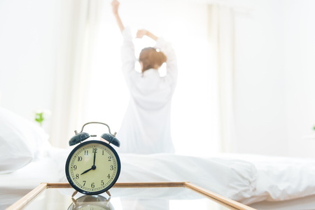 Vue arrière de la femme qui s'étend le matin après s'être réveillé sur le lit près de la fenêtre avec réveil. Concept de vacances et de détente. Concept de journée et de jour férié. Bureau femme et travailleur dans le thème de la vie quotidienne Banque d'images