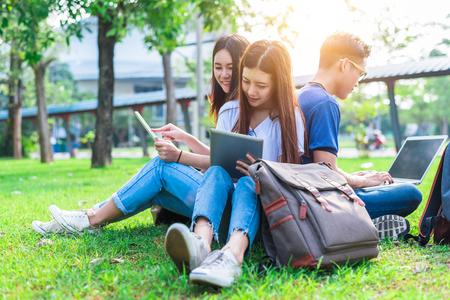 Grupo de estudante universitário asiática que usa a tabuleta e o portátil no campo de grama no ar livre. Conceito de aprendizagem de tecnologia e educação. Tecnologia do futuro e conceito de entretenimento moderno. Tema edutainment.