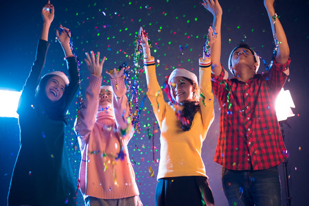 Group of Asian people celebrating New year party in night club with confetti. New year and Christmas party concept. Happiness and Entertainment concept. Night pub and Night life theme. New year 2018 Foto de archivo