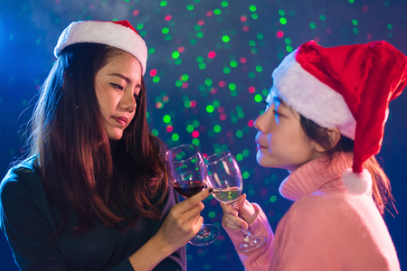 Two Asian woman celebrating Christmas and New year party with toasting wine glasses in pub. People and Night life concept. Party and Event theme. Clink glasses together Stock Photo