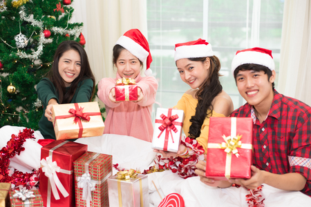 Group of young Asian people holding and giving gift box to you with Xmas tree background. Holiday and Festival concept. Christmas and New year event theme. Happy people wearing Santa hat. Stock Photo