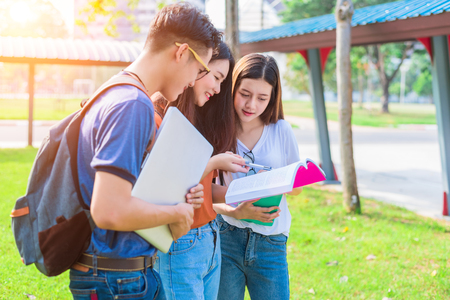 Three Asian young campus people tutoring and preparing for final examination in university. Education and learning concept. Friendship and Relation ship concept. College and Outdoors theme. Banque d'images