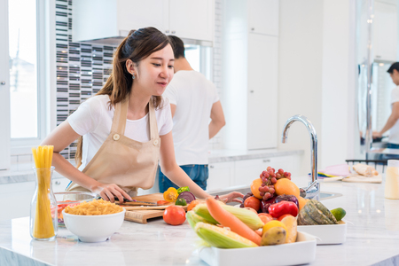 Asian lovers or couples preparing and looking for necessary ingredients in kitchen with full of ingredient on table. Honeymoon and Happiness concept. Valentines day and Sweet home concept Stock Photo