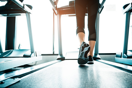 Close up of people who exercising on treadmill. Close-up of woman legs walking by treadmill in sports club. Fitness and Body build up concept. Workout and Strength training concept. Sport club theme.