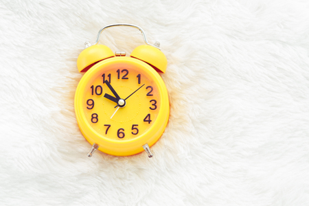 Yellow alarm clock on white wool. Late and Lazy time concept. Morning in holiday theme. Around 10 O Clock Banco de Imagens