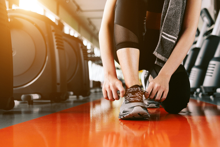Sport woman tying sneakers rope. Sport center and Fitness gym concept. Healthy and Body build up theme. Sport wear and Fashion theme Stock Photo