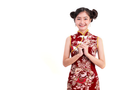 Young Asian beauty woman wearing cheongsam and blessing or greeting gesture in Chinese new year festival event on isolated white background. Holiday and Lifestyle concept. Qipao dress wearing