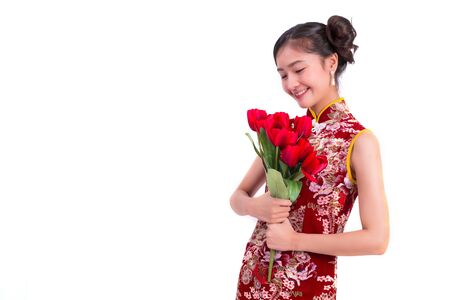 Young Asian beauty woman wearing cheongsam and holding red rose gesture in Chinese new year and Valentines festival event on isolated white background. Love festival and Lifestyle concept. Qipao dress