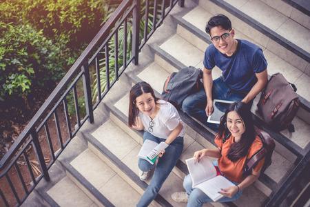 Tres jóvenes estudiantes asiáticos del campus disfrutan de la tutoría y leen libros juntos en la escalera. Concepto de amistad y educación. Campus escolar y tema universitario. La felicidad y la diversión de aprender en la universidad. Foto de archivo - 95508448