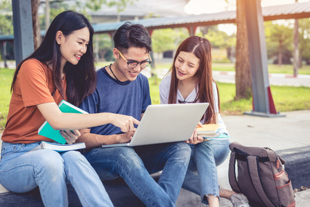 Three Asian young campus students enjoy tutoring and reading books together. Friendship and Education concept. Campus school and university theme. Happiness and funny of learning in college