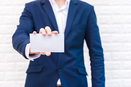 Business man showing white paper. Man  wearing blue suit and holding white blank card. Lifestyle and working concept. Business and object theme. Blank space in paper for insert text.