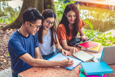 Group of Asian college student reading books and tutoring special class for exam on table at outdoors. Happiness and Education learning concept. Back to school concept. Teen and people theme.