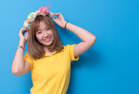 Beauty woman posing with flower hat in front of blue wall background. Summer and vintage concept. Happiness lifestyle and people portrait theme. Cute gesture and pastel tone.
