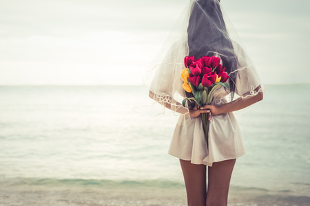 Asian woman holding flowers in behind and waiting for someone make her happy. Lonely and single woman concept. Sadness and soulmate concept. Dark ton film filter. Heart broken and wedding theme. Stock Photo