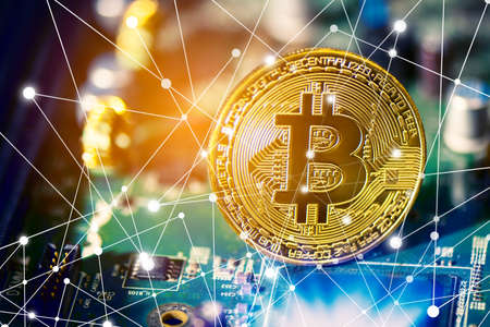 Bitcoin on electronic circuit board. Cryptography and Electronic money concept. Currency trading and Gold mining theme. Business and Technology theme. Network line dot link and light elements