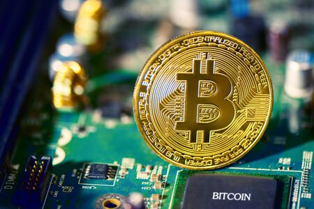 Bitcoin on electronic circuit board. Cryptography and Electronic money concept. Currency trading and Gold mining theme. Business and Technology theme.