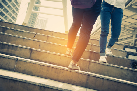 Close up legs of two traveling people walking on stepping up stair in modern city. Sneakers and jeans elements. Business and travel concept. City lifestyle and working people theme. Rush hours theme. Banque d'images