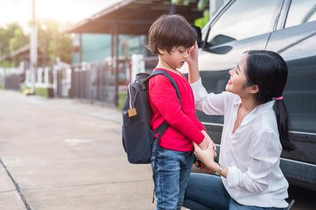 Moeder bereidt zich voor om haar kinderen 's ochtends met de auto terug naar school te sturen. Onderwijs en terug naar school-concept. Gelukkig gezin en liefdevolle mensen thema.