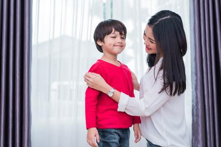 La giovane mamma asiatica ha vestito la camicia del figlio per preparare andare a scuola. Concetto di madre e figlio. Famiglia felice e tema casa dolce casa. Tema prescolare e ritorno a scuola.