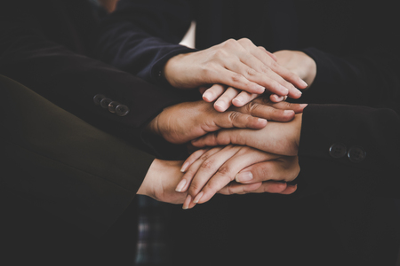Business people making pile of hands for startup new project. Business and togetherness concept. Cooperation and Successful concept. Teamwork and Organization theme. Close up view of stacking hands. Stock Photo