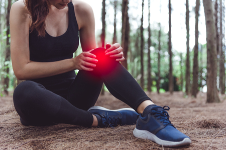 Sport woman injury at knee during jogging in forest. Pine woods background.  Medical and Healthcare concept. Nature and People theme. Lifestyles theme. Red light spot use Stock Photo