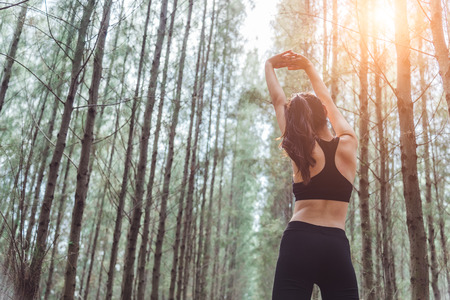 Women stretching arms and breathing fresh air in middle of pinewood forest while exercising. Workouts and Lifestyles concept. Happy life and Healthcare theme. Nature and Outdoors theme. Back view