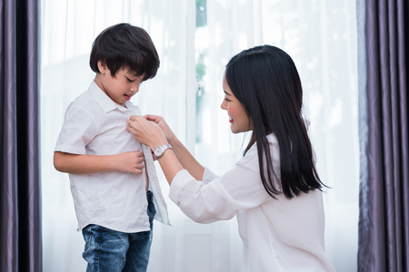 Young Asian mom dressed up son outfits for preparing go to school. Mother and son concept. Happy family and Home sweet home theme. Preschool and Back to school theme. Banco de Imagens