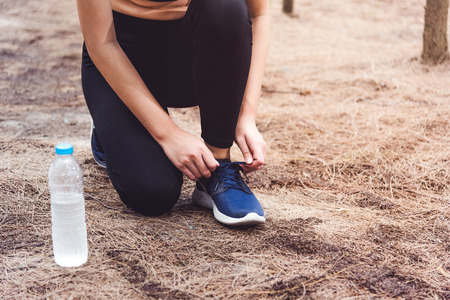 Woman tying up shoelaces when jogging in forest back with drinking water bottle beside hers. Sneakers rope tying. People and lifestyles concept. Healthcare and Wellness theme. Park and Outdoors theme.