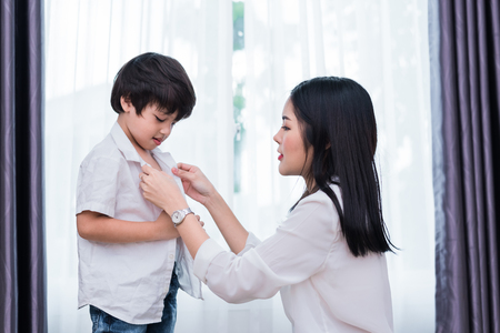 Young Asian mom dressed up son outfits for preparing go to school. Mother and son concept. Happy family and Home sweet home theme. Preschool and Back to school theme. 스톡 콘텐츠