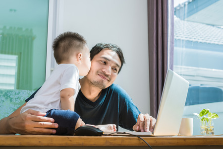 Son kissing his father while using internet. People and Lifestyles concept. Technology and Happy family theme. Single dad theme. Foto de archivo