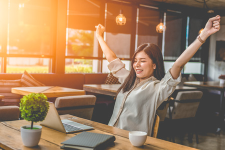 Beauty Asian woman raising two hands after finishing job happily with laptop computer. People and lifestyles concept. Technology and Business working theme. Occupation and coffee shop theme. Stock Photo