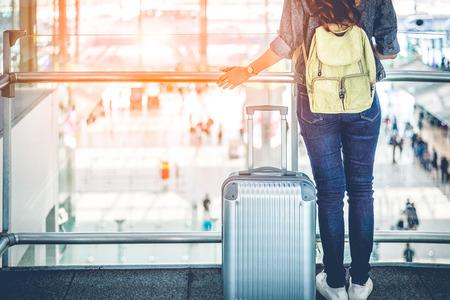 Zamknij się z dolnej części ciała podróżnika czekając na lot startu w wysokim terenie na lotnisku terminalu. Koncepcja ludzie i styl życia. Motyw biznesowy i podróżniczy.