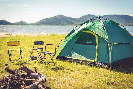 Camping tent with extinguished bonfire in the green field meadow, Lake and mountain background. Picnic and travel concept. Nature theme. Stock Photo