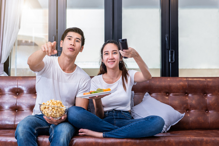 Asisn couples watching television together on sofa in their home. People and lifestyles concept. Vacation and holiday concept. Honeymoon and pre-wedding theme. Happy family activity theme