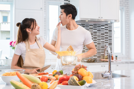 Asian couples feeding food together in kitchen. People and lifestyles concept. Sweet honeymoon and Holidays concept. Valentines day and wedding theme. Puppy love and romantic theme. Stock Photo - 107205310
