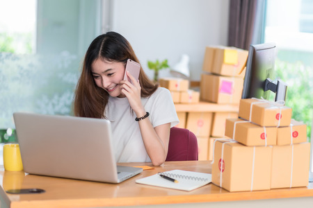 Asian woman enjoy herself while using  internet on laptop and phone in office. Business and marketing and part time concept. Online shopping and business success theme. Happy mood doing working job.