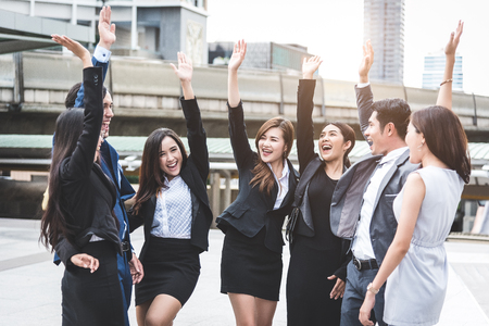 Portrait of successful group of business people at outdoor urban. Happy businessmen and businesswomen raising hand as team in satisfaction gesture. Successful group of people smiling after achievement