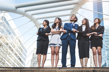 Portrait of successful group of business people looking up to sky as future. Happy businessmen and businesswomen team in satisfaction gesture. Successful group of people smiling in city background