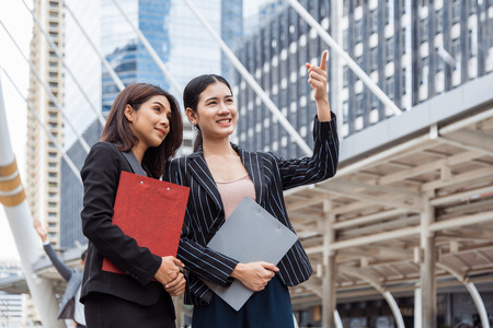 Two young businesswomen looking and pointing forward for thinking of future plan and sale break even point after marketing. Business teamwork employees of lifestyle working women. Boss and secretary