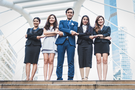 Portrait of successful group of business people at outdoor urban. Happy businessmen and businesswomen standing as team in satisfaction gesture. Successful group of people smiling and looking at camera
