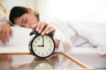 Asian young beauty woman turning off alarm clock in morning late without looking clock and lazy to working on in holiday. Bedroom and bed time concept. Relaxation and people lifestyles of tired worker
