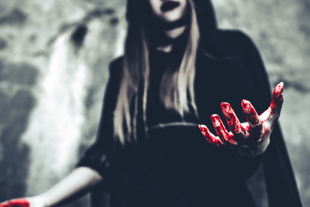 Witch showing bloody hand. Female demon angel in black clothes and hood on grunge wall background. Halloween day and Mystery concept. Fantasy of magic theme. Afterlife and Death concept.
